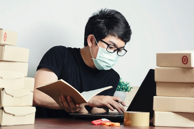 Asian man small business owner work from home and wear a mask to protect against corona virus. online marketing, startup sme concept. Premium Photo