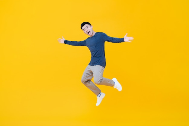 Asian man smiling and jumping with arms outstretched Premium Photo