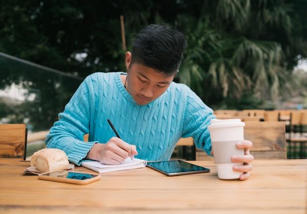 Азиатский человек учится в кафе. Premium Фотографии