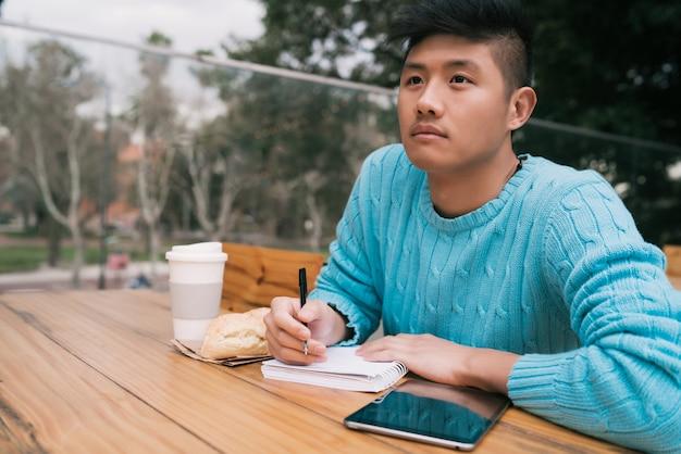 Азиатский человек учится в кафе Premium Фотографии