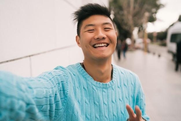 Asian man taking a selfie. Free Photo