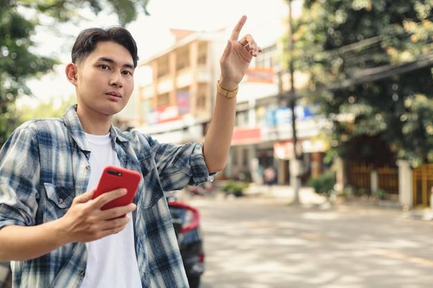 Азиатский мужчина ждет такси uber Premium Фотографии