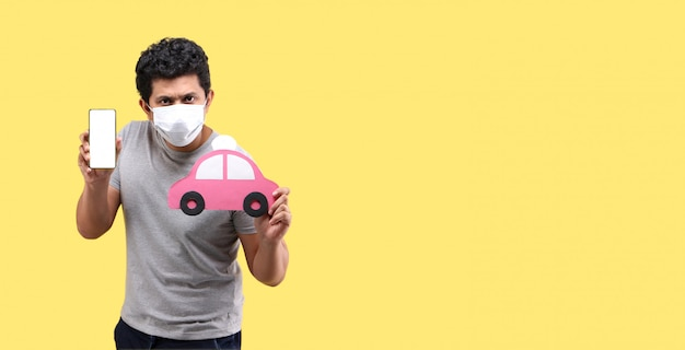 Азиатский человек, носящий маску, держит смартфон и руку держит красный бумажный автомобиль на желтой стене Premium Фотографии