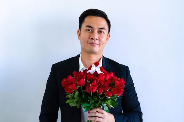 Азиатский мужчина в черном костюме держит букет красных роз и красную подарочную коробку, изолированную на белом фоне для годовщины или концепции дня святого валентина. Premium Фотографии