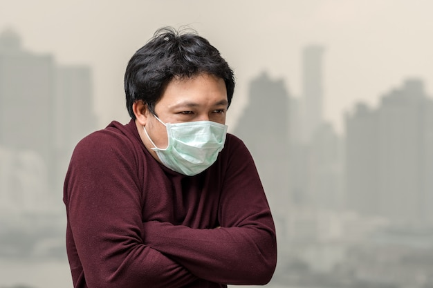 Premium Photo | Asian man wearing the face mask against air pollution with  cold at the balcony