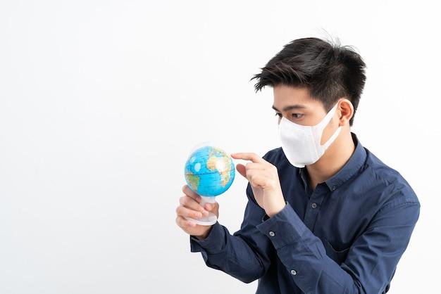 Uomo asiatico che indossa la maschera per il viso che tiene in mano la mappa della mappa del mondo del globo Foto Gratuite
