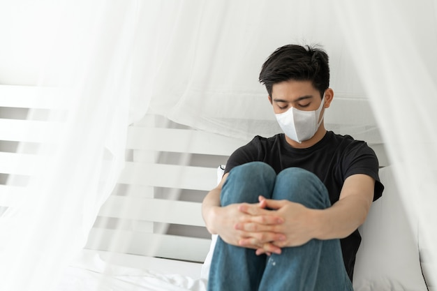 Азиатский мужчина носит маску для лица для защиты от головной боли и кашля из-за коронавируса covid-19 в карантинной комнате Бесплатные Фотографии