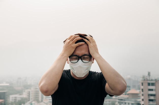 Asian man wearing hygiene mask and sick because of air pollution in the city. Premium Photo