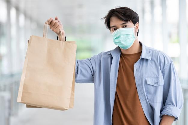 Asian man wearing medical face mask holding shopping bag Premium Photo