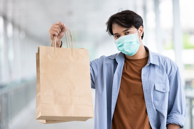Asian man wearing protective face mask holding shopping bag during coronavirus disease outbreak, new normal lifestyle. Premium Photo