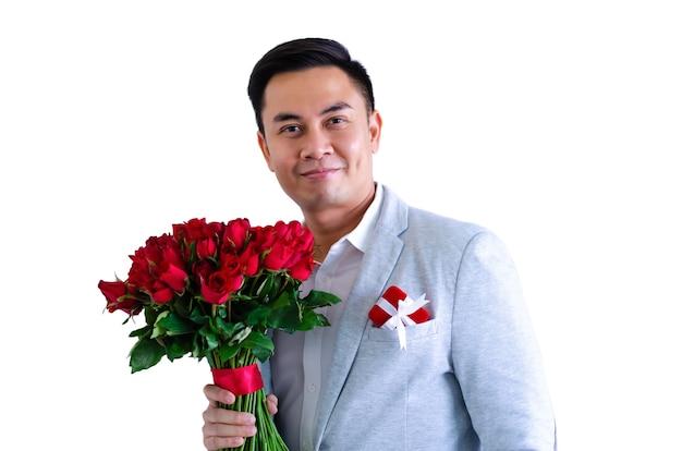 Азиатский мужчина с букетом красных роз и подарочной коробкой для концепции дня святого валентина. Premium Фотографии
