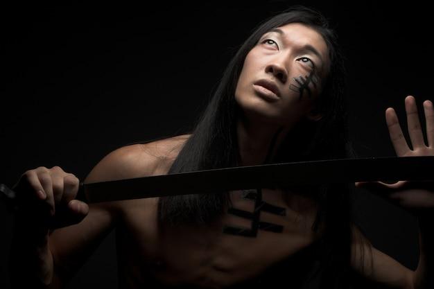 Азиатский мужчина с катаной Premium Фотографии