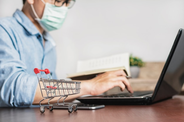 Asian man working at home office and wear a mask to protect against corona virus Premium Photo