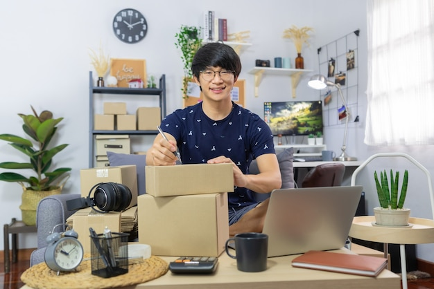 Asian man working sell online writing address on package of orders Premium Photo