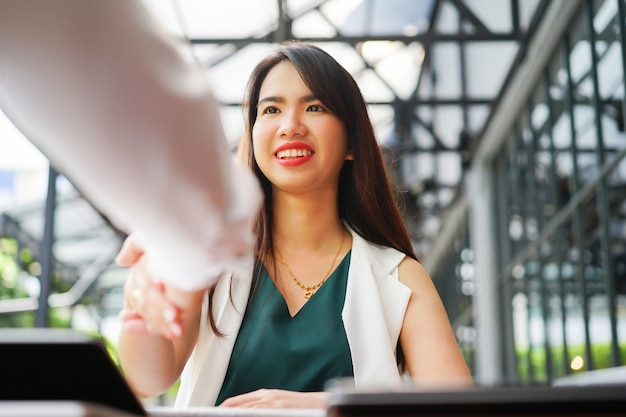 Asian manager woman hand shake with graduated person after job interview Premium Photo