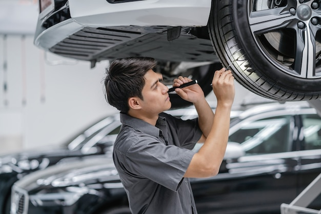Asian mechanic checking and torch tire in maintainance service center which is a part of showroom Premium Photo