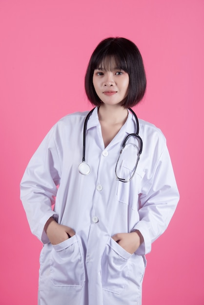 Asian medical doctor woman with white lab coat on pink Free Photo