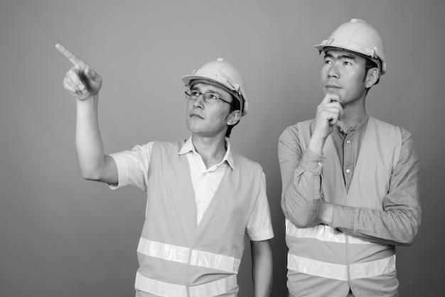 Азиатские мужчины на стройке вместе изолированные Premium Фотографии