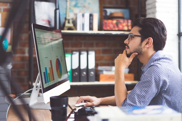 Asian men is watching a graph from a computer in the office. Premium Photo