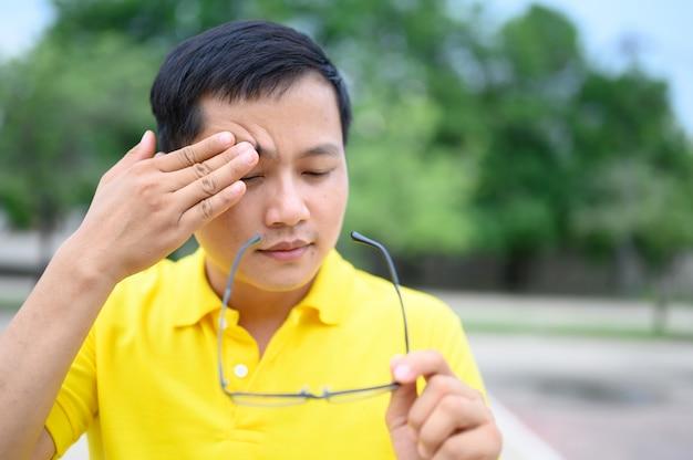 Asian men wear yellow shirts with stress, eye strain. Premium Photo