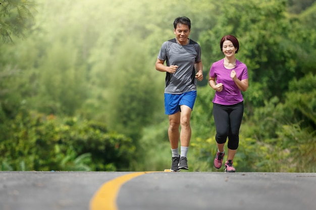 Premium Photo | Asian middle aged couple jogging exercise in park