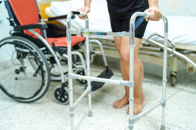 Asian middle-aged lady woman patient walk with walker at nursing hospital ward. Premium Photo