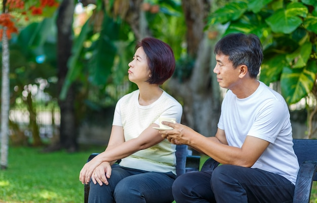 Asian middle aged male asking to make up with his wife Premium Photo