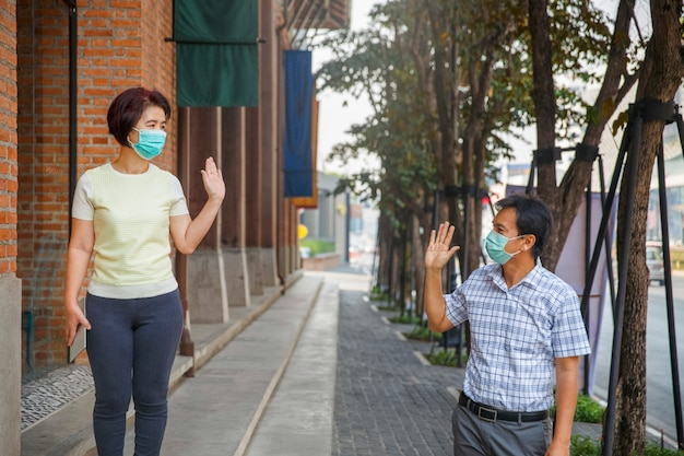 Asian middle aged people wearing mask and keep social distancing ...