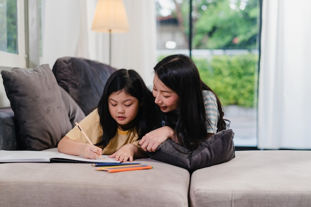 Asian middle-aged woman teach her daughter do homework and drawing at home. lifestyle mother and kid happy fun spend time together in living room in modern home in the evening . Free Photo