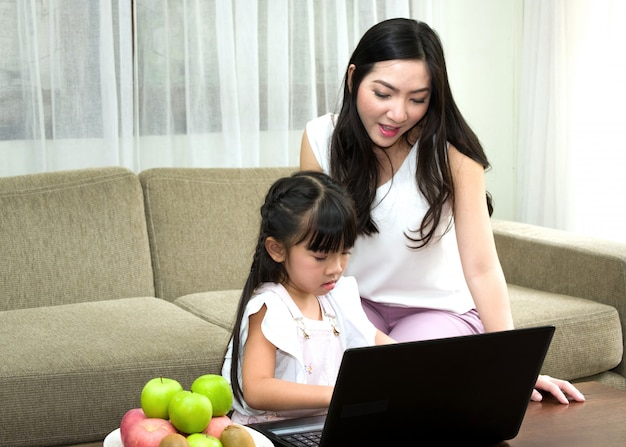 Asian mom is teaching their daughter to type the keyboard on the Premium Photo