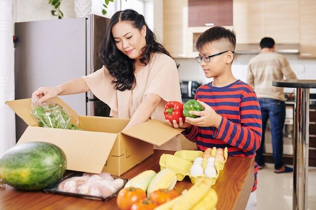 아시아 어머니와 아들이 식탁에서 신선한 식료품 상자를 풀고 프리미엄 사진