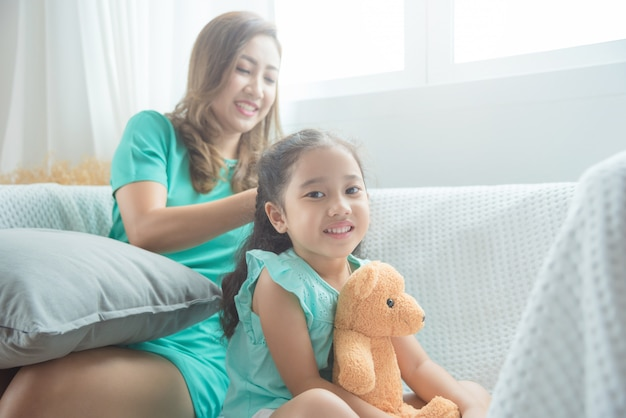 Asian mother braiding hair to her daughter before going to school Premium Photo