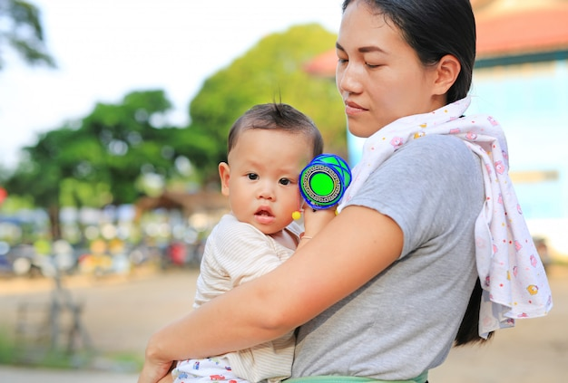 Asian mother carrying her infant baby boy outdoor. Premium Photo