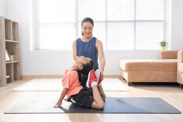 Asian mother and daughter exercising at home they are doing yoga Free Photo
