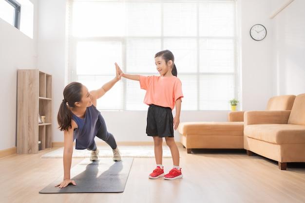 Madre asiatica e figlia che esercitano a casa stanno divertendosi insieme Foto Gratuite