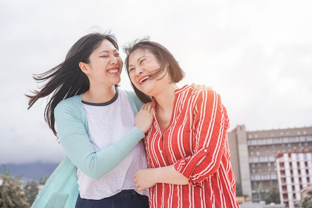 Asian mother and daughter having fun outdoor - happy family people enjoying time together around city in asia Premium Photo