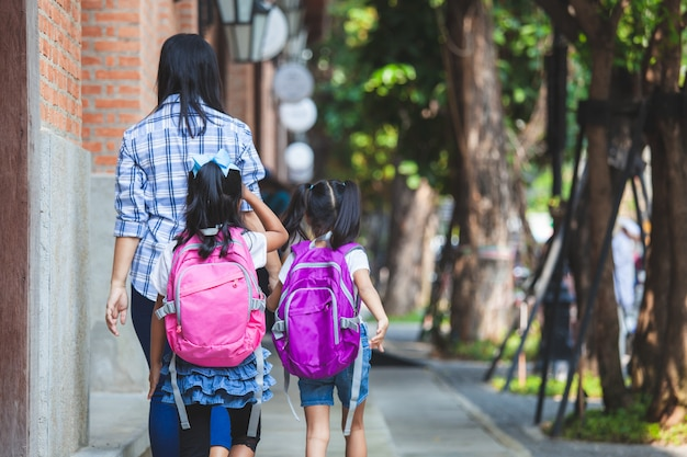 Asian mother and daughter pupil girl with backpack holding hand and going to school together Premium Photo