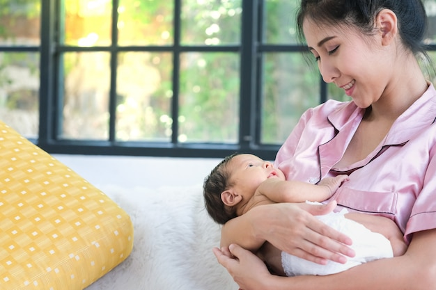 Asian mother holding a 1.5-month-old child Premium Photo