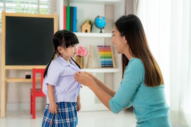 Premium Photo | Asian mother preparing kindergarten student uniform