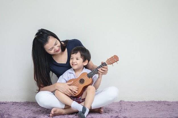 Asian mother teach her son to play ukulele Premium Photo