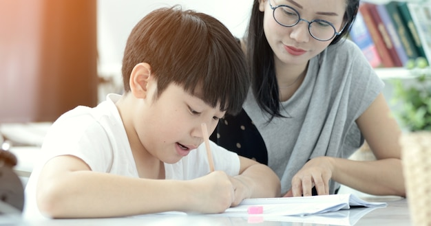 Asian mother with son doing homework in living room. Premium Photo