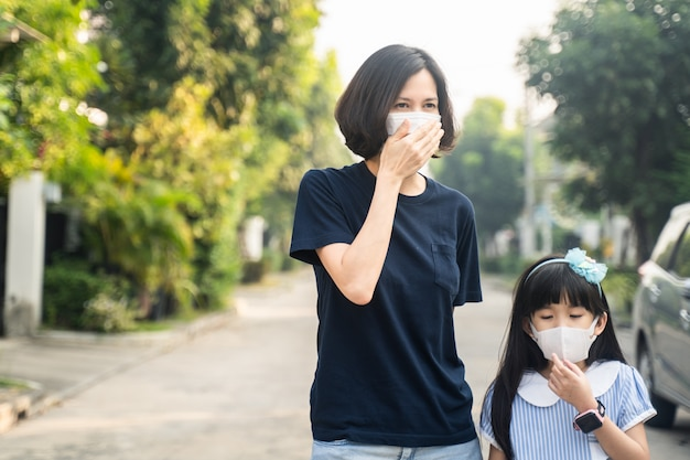 Asian mother woman and little young girl daughter wearing mask for prevent covid-19 Premium Photo