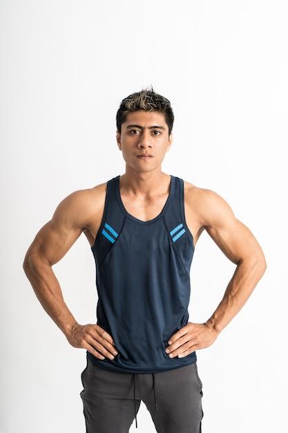 Азиатский мускулистый мужчина в спортивной одежде стоит лицом вперед, положив руки на талию Premium Фотографии
