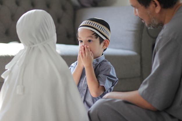 伝統的な衣装を着たアジアのイスラム教徒の家族。神に祈った後、家に子供がいるイスラム教徒の父。ラマダンの聖なる月のイスラム教徒の人々の概念。 Premium写真