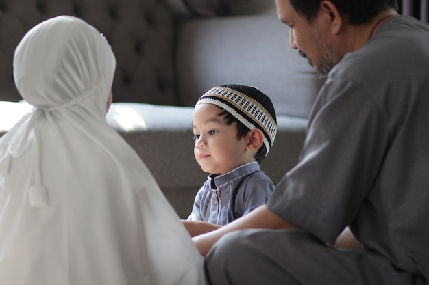 Asian muslim family in traditional costume.muslim father with kids in their house after pray to god.concept of muslim people in ramadan holy month. Premium Photo