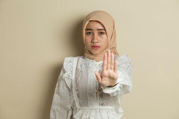 Азиатская мусульманская женщина в хиджабе показывает жест рукой Premium Фотографии