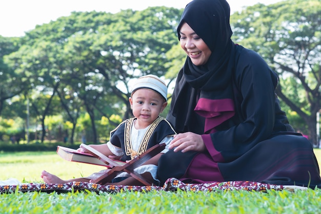 Asian muslim kid is reading the quran in the park, muslim mom and son concept Premium Photo