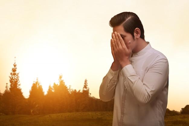Азиатский мусульманин с традиционным платьем молится Premium Фотографии