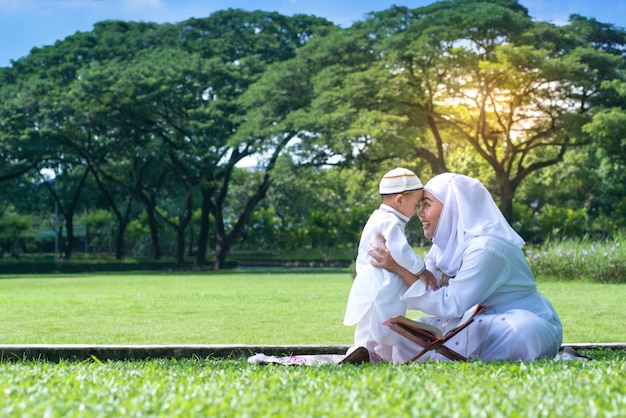 Asian muslim mother and her son smiling, hugging and kissing together Premium Photo