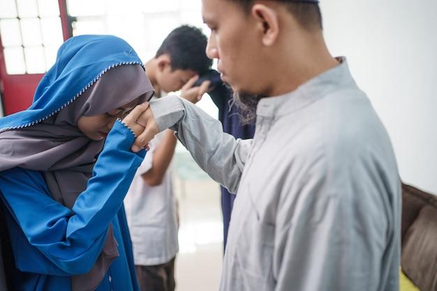 アジアのイスラム教徒の親がイドゥルフィトリイードムバラクで手を振る Premium写真